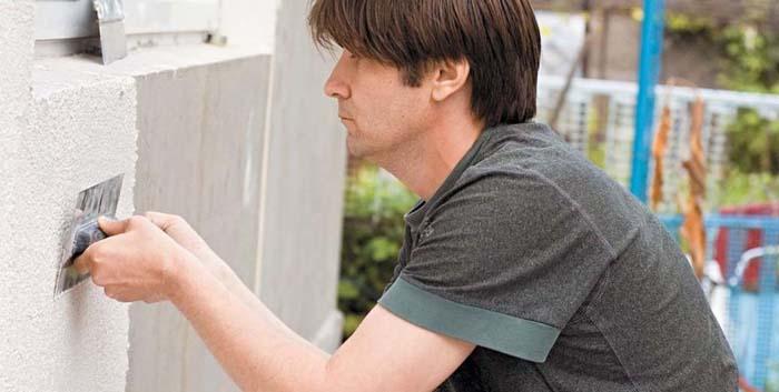 На фото мужчина использует фасадную шпатлевку