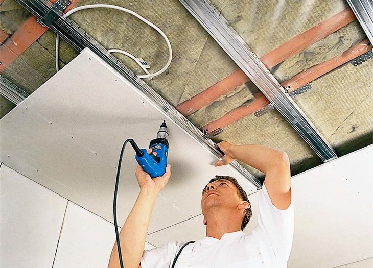На фотографии установка потолочных плит подвесного потолка