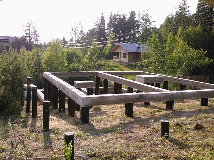 На фото столбчатый фундамент из древесины