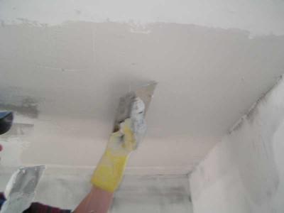 На изображении процесс выравнивания неровностей на потолке