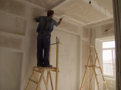 На снимке процесс нанесения штукатурки на потолок