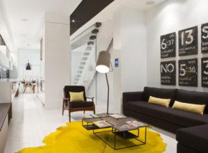 Жёлтый ковёр в белой гостиной с тёмной мебелью