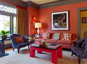 Белёсый восточный ковёр в гостиной с оранжевыми стенами и синей мебелью