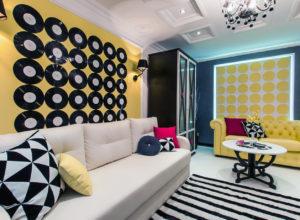 Полосатый чёрно-белый ковёр в гостиной с жёлтыми и и синими стенами