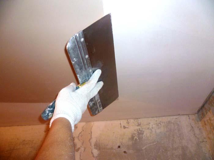 Фотография процесса грунтовки потолка