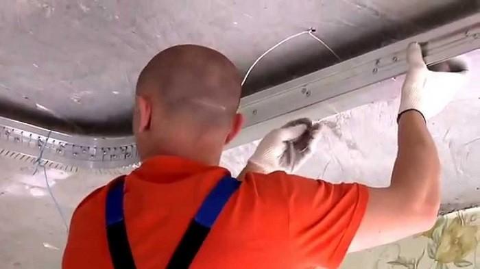 На фото установка натяжного потолка с подсветкой