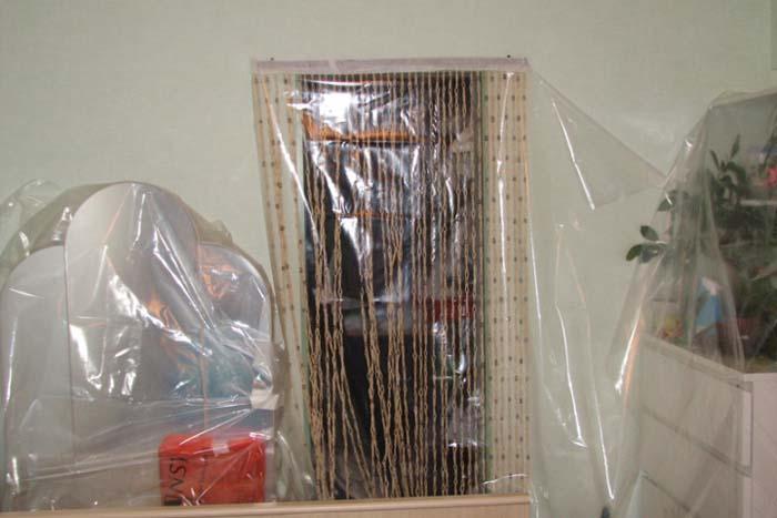На фотографии защита мебели от пыли пленкой
