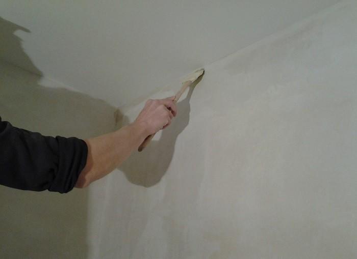 На снимке нанесения клея на стену