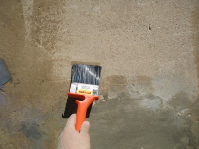 На фото процесс нанесения грунтовки на стену кисточкой