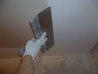 На фото процесс шпаклевки потолка