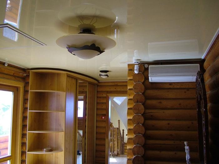 На фото натяжной потолок в деревянном доме