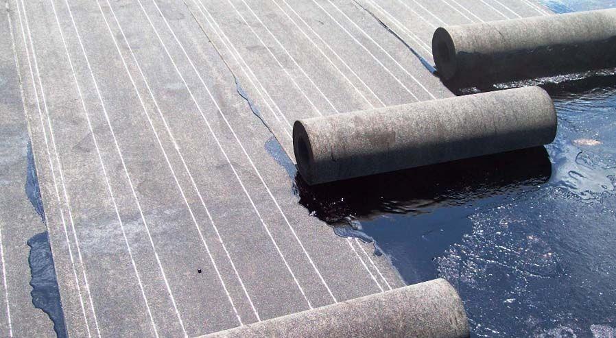 Процесс укладки рубероида на крышу