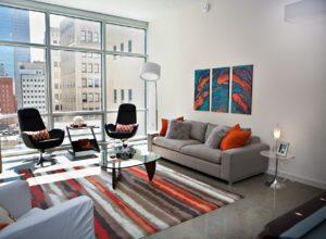 Полосатый ковёр в гостиной с серым диваном и окном во всю стену