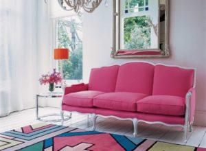 Пёстрый ковёр в комнате с розовым диваном