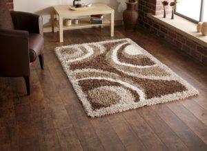 Уголок монохромной гостиной в оттенках коричневого с пушистым ковриком у кресла